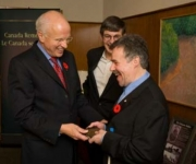 Honourable Greg Thompson, then Minister of Veterans Affairs presents Terry Kelly with a commemorative Vimy coin